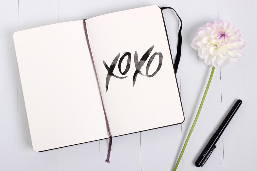 Sketchbook mockup with pen and flower